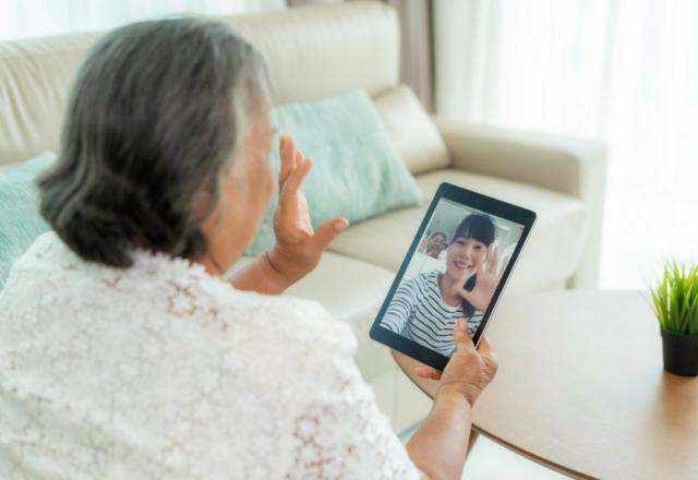 Elderly woman uses tablet to video chat