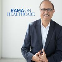 Mohan Nair standing in front of a white background with the RamaOnHealthcare logo next to him